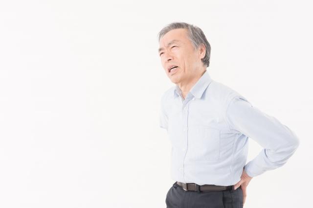 腰痛でつらそうな男性の写真